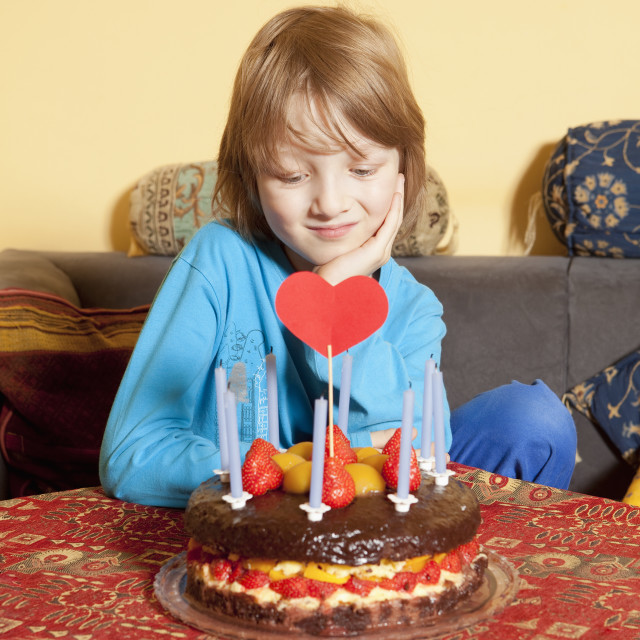 """""""Boy with Blond Hair Looking at his Birthday Cake"""" stock image"""