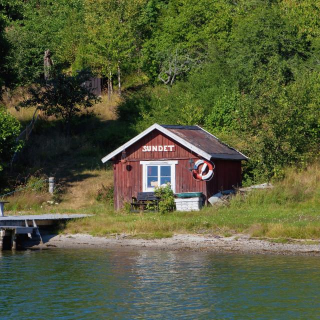 """Sweden, Stockholm - Little red house on island in archipelago."" stock image"