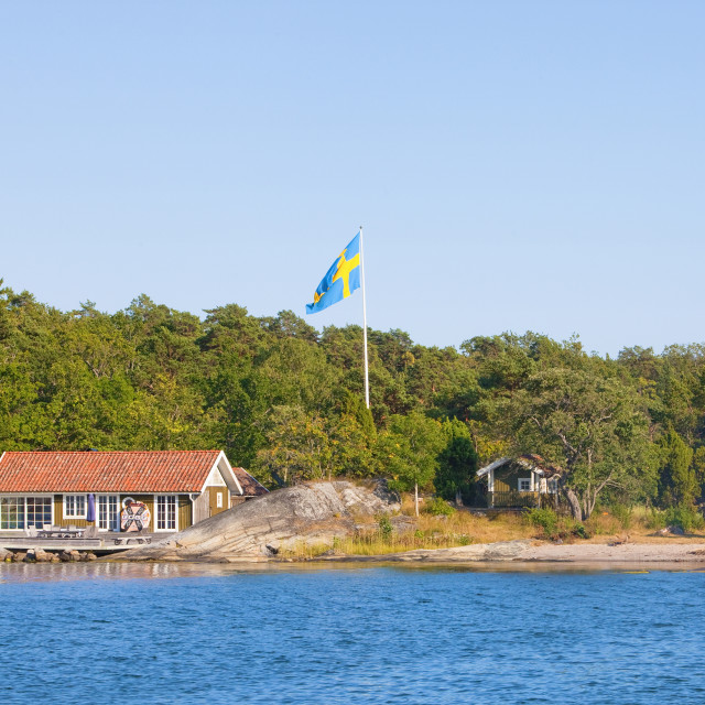 """Sweden, Stockholm - House on island in archipelago with swedish flag on pole."" stock image"
