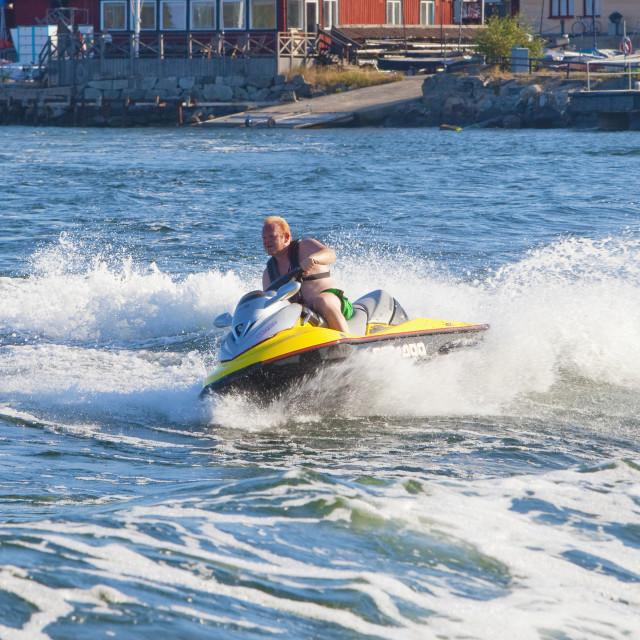"""Sweden, Stockholm - Man riding personal watercraft jet ski in archipelago."" stock image"