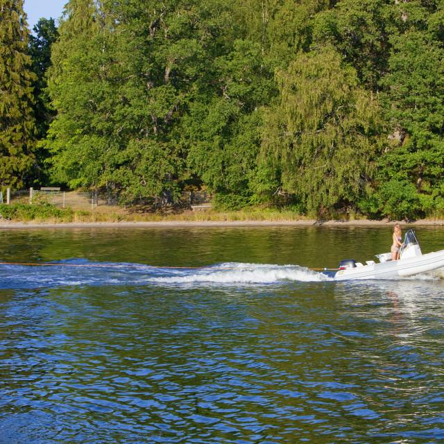 """Sweden, Stockholm - Mother in motorboat pulling kids in rubberboat."" stock image"