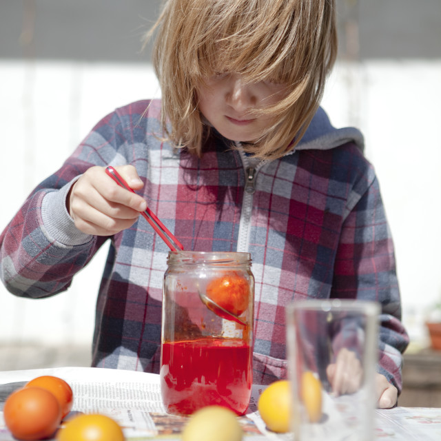 """""""Boy Coloring Easter Eggs by Putting Them in Glasses with Color"""" stock image"""