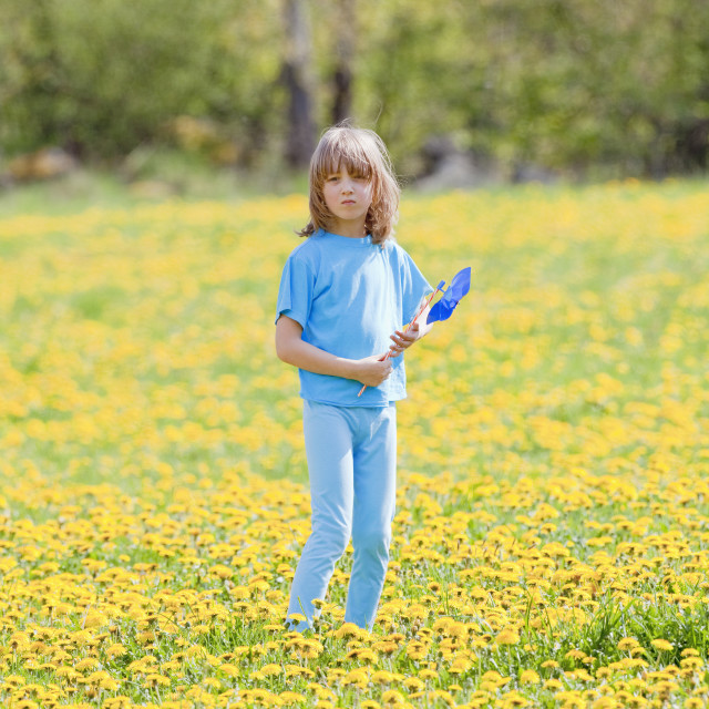 """""""Boy with Pinwheel in a Meadow of Dandelions"""" stock image"""