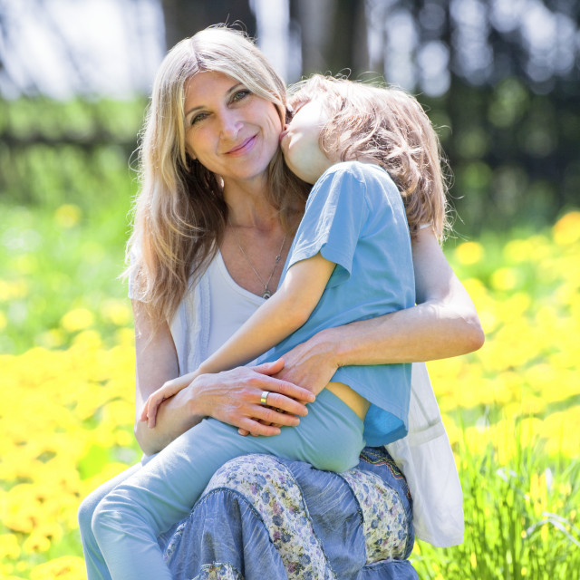 """Boy Embracing his Mother, Sitting on her Lap in Garden"" stock image"