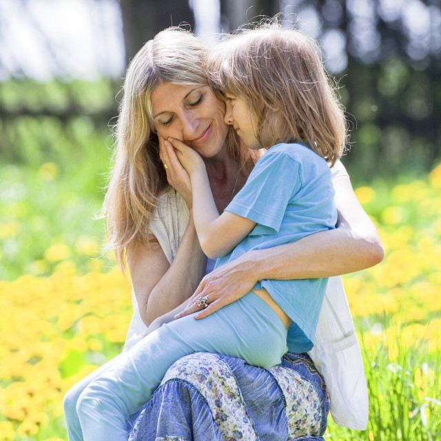 """""""Boy Embracing his Mother, Sitting on her Lap in Garden"""" stock image"""