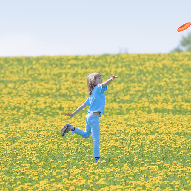 """Boy Throwing Frisbee in Meadow of Dandelions"" stock image"
