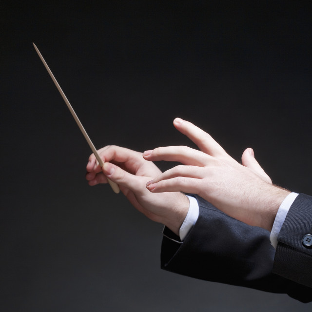 """Hands of Conductor with Baton Leading Orchestra"" stock image"