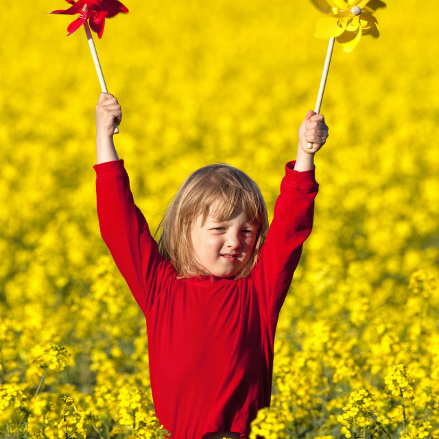 """""""boy with long blond hair playing with pinwheels in canola field"""" stock image"""