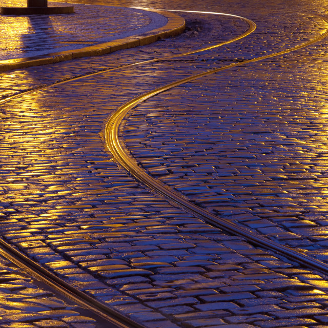 """prague - tram tracks and cobblestone street at dusk after rain"" stock image"