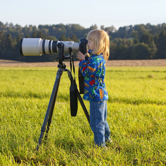 """boy looking through super telephoto lens on digital camera"" stock image"