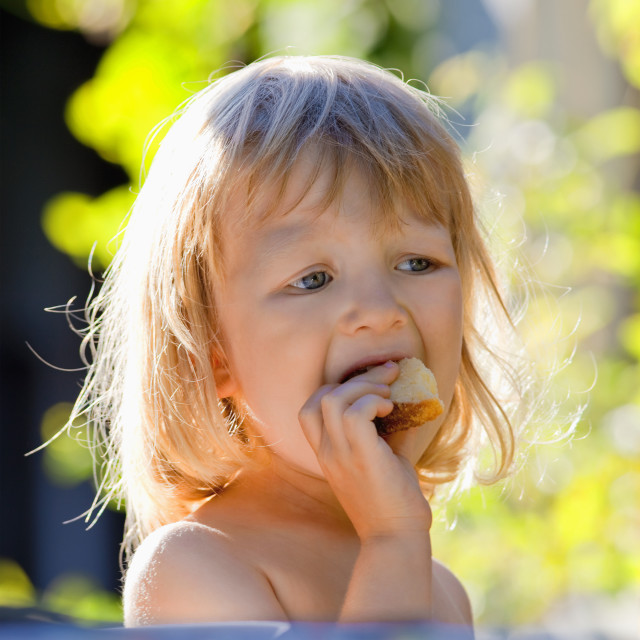 """boy with long blond hair eating in the garden"" stock image"