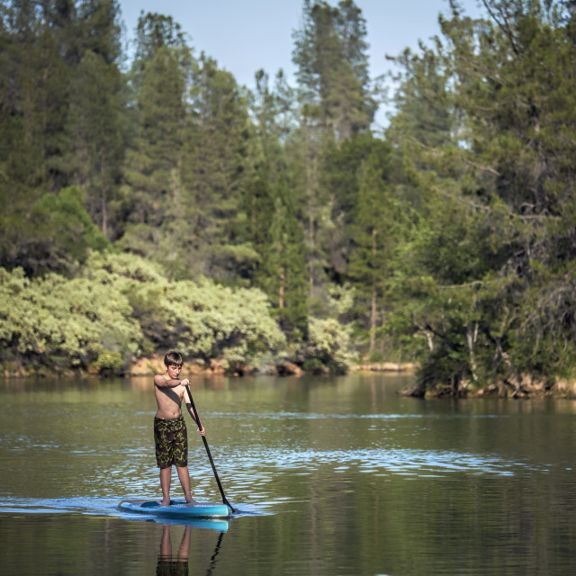 """A Young Boy Paddling a Stand Up Paddle Board on a Lake."" stock image"