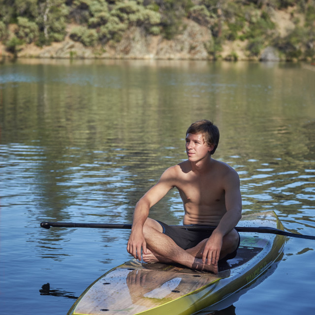 """""""A Teenage Boy Resting on a Paddle Board on a Summer Afternoon"""" stock image"""