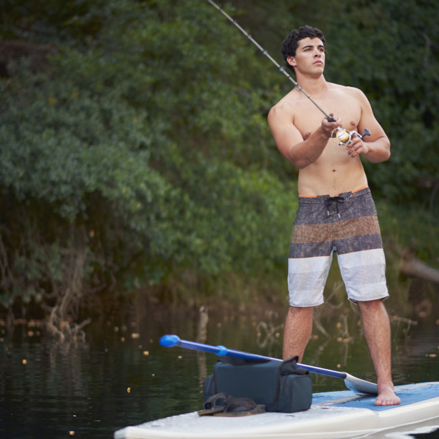 """""""Fisherman casting a line from his paddle board."""" stock image"""