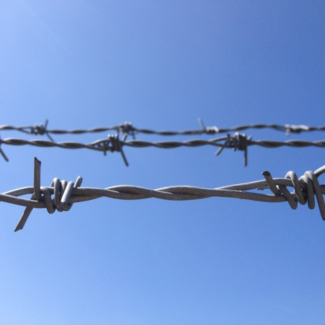 """Barbed wire against blue sky"" stock image"