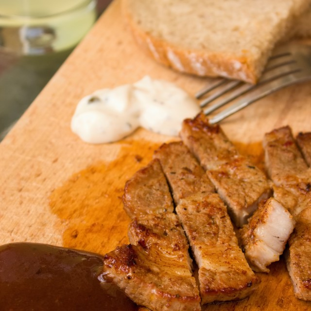 """BBQ sauce with pork steak portion on wooden chopping board"" stock image"