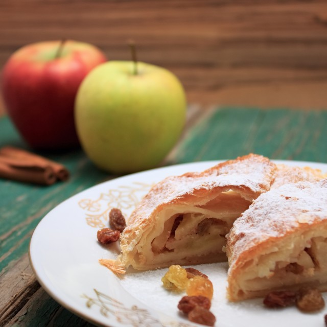 """Apple pie strudel on white plate with gold ornament"" stock image"