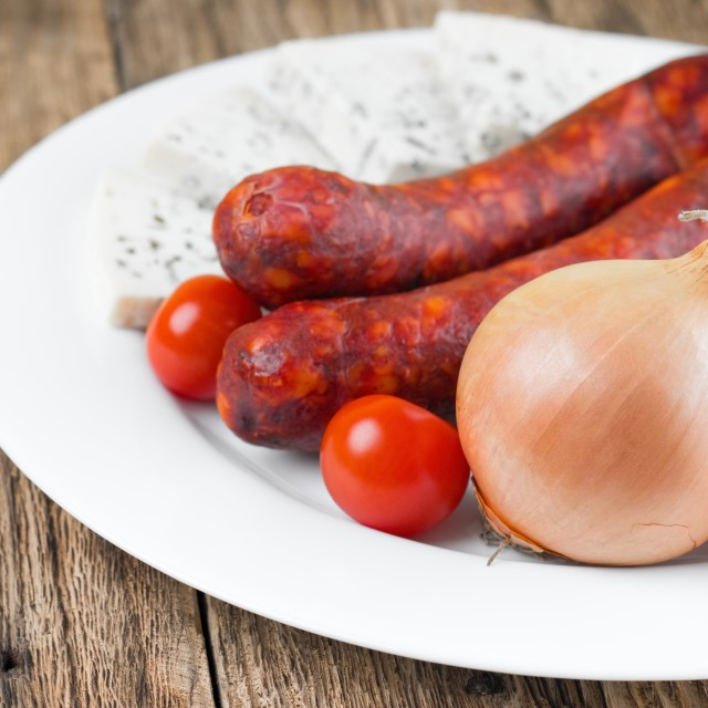 """Big raw onion on plate with sausages"" stock image"