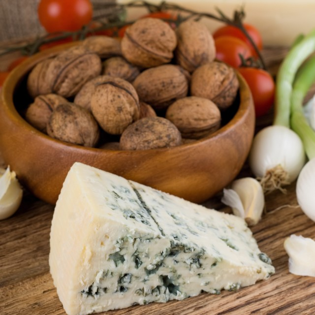 """Big portion of niva cheese in front of various vegetable"" stock image"