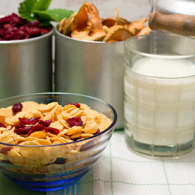 """Blue glass bowl with cornflakes in front of old cups"" stock image"