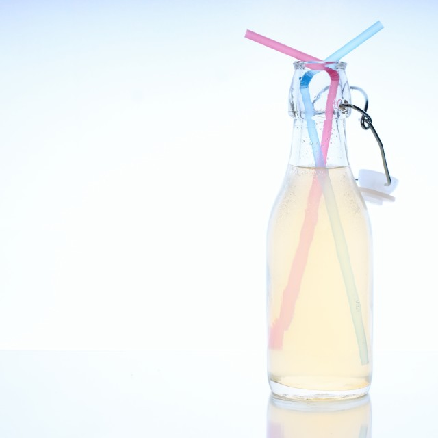 """Bottle with cold drink on glass table with two straws"" stock image"