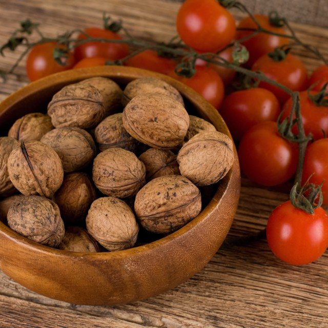 """Bowl full of walnuts and branch with tomatoes"" stock image"