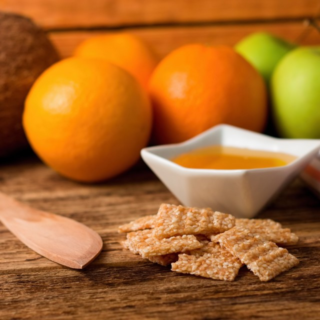 """Broken sesame biscuits in front of honey and fruit"" stock image"