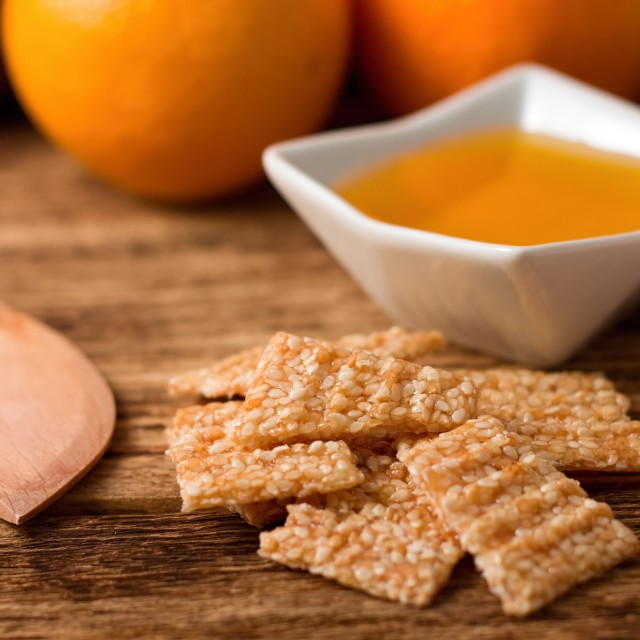 """Broken sesame wafers in front of bowl with honey"" stock image"