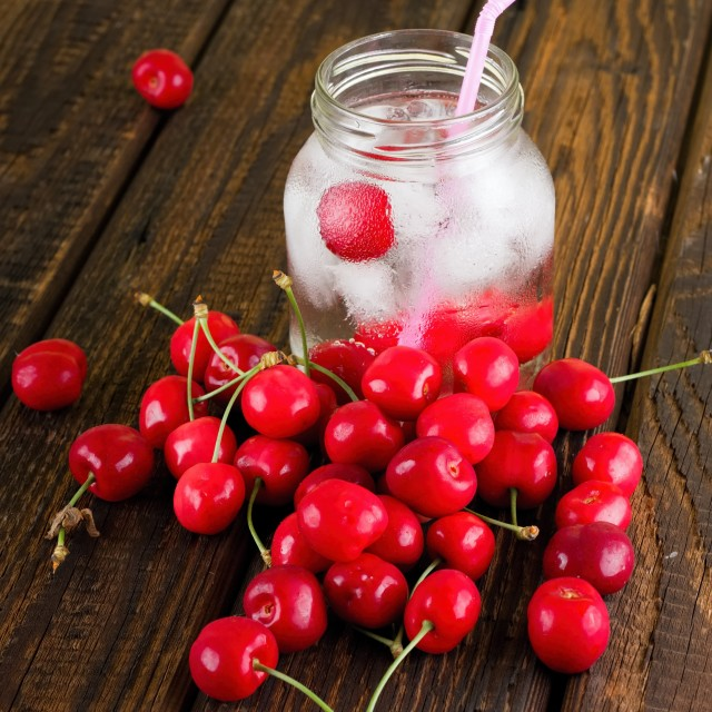 """Cold drink in a jar with pink straw among several cherries"" stock image"
