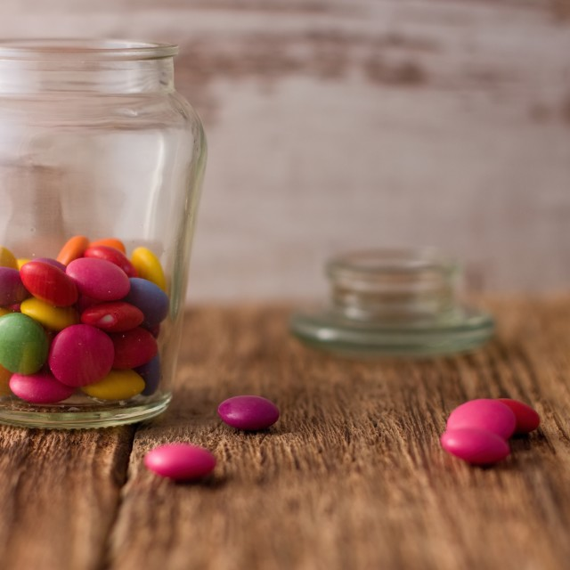 """Color chocolate smarties in glass dose and around on wooden board"" stock image"