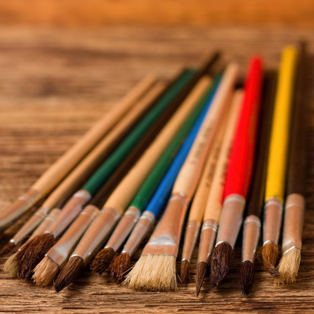 """Color paintbrushes on vertical photo placed on wooden board"" stock image"