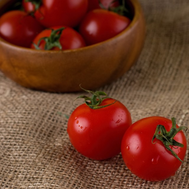 """Couple of red juicy tomatoes in front of bowl full of others"" stock image"