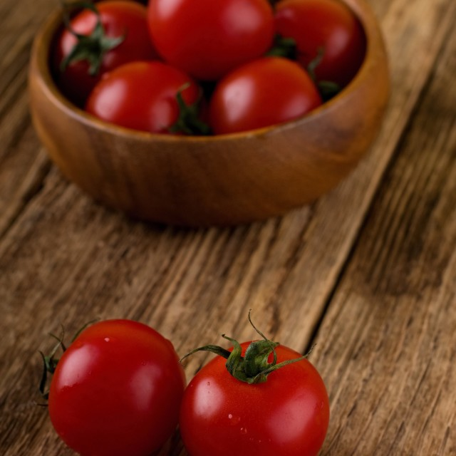 """Couple of red tomatoes in front of bowl with others"" stock image"