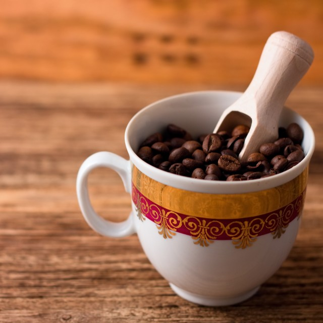 """Cup full of coffee grains and wooden spoon"" stock image"