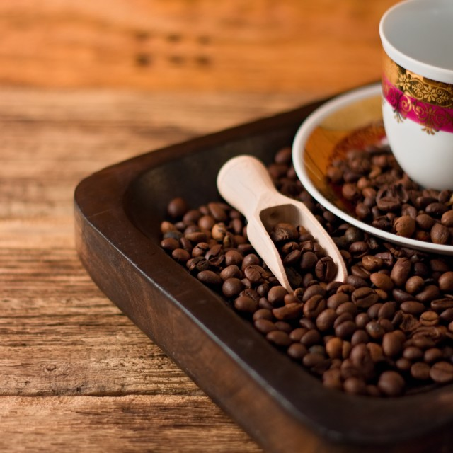 """Cup with plate on tray full of coffee beans"" stock image"