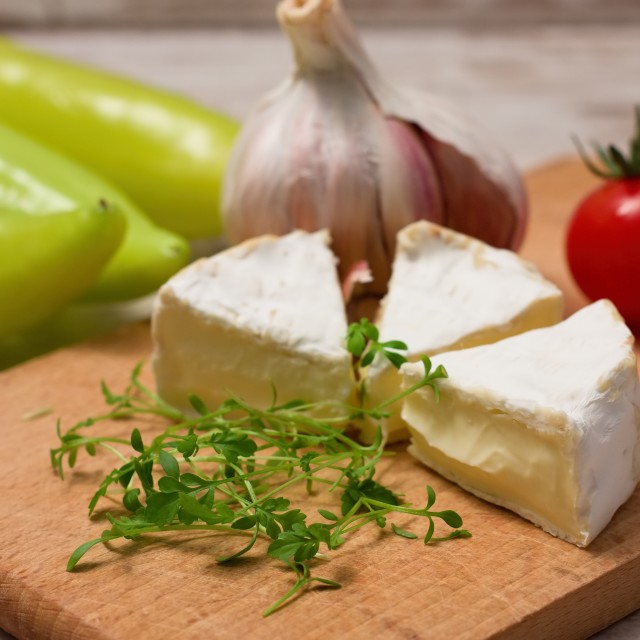"""Cress shoots in front of camembert portions"" stock image"