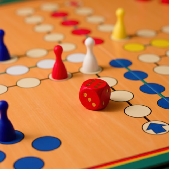 """Dice with six up among figurines on ludo"" stock image"