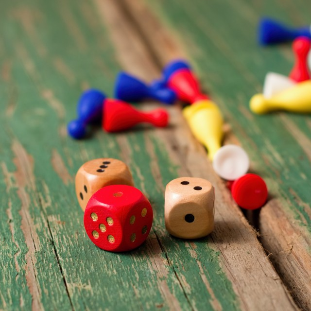 """Few dices and color figurines on green wooden board"" stock image"