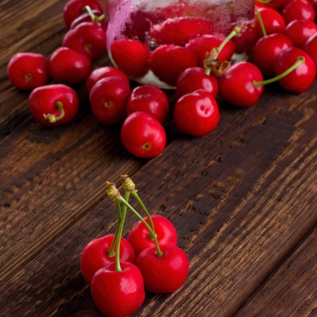 """Four cherries on wooden board in front of others"" stock image"