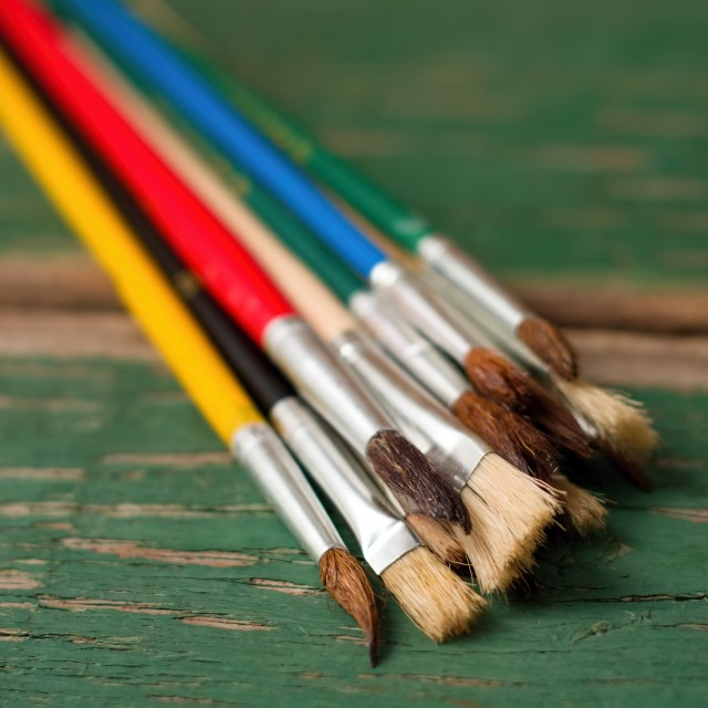 """Paintbrushes placed on green worn wooden board"" stock image"