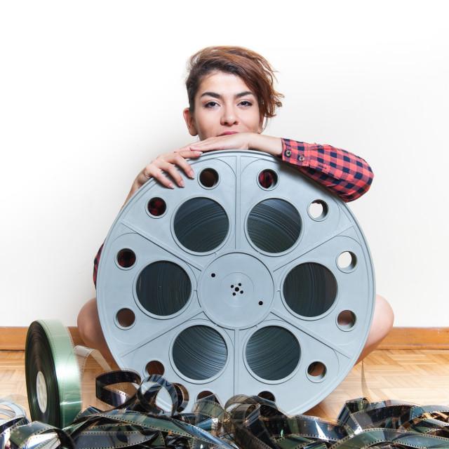 """Young woman sitting behind big cinema movie reel"" stock image"