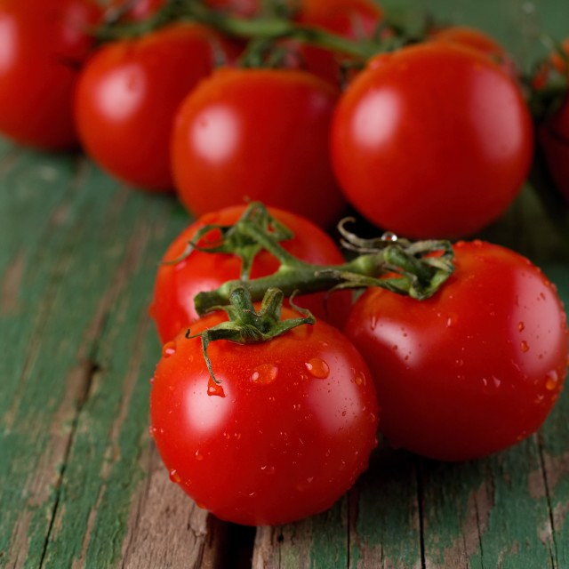 """""""Three red juicy tomatoes on board with worn green color"""" stock image"""