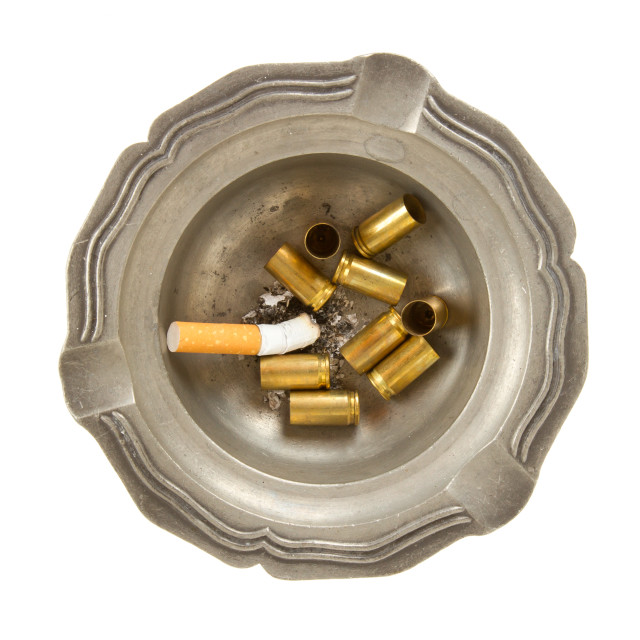 """""""Empty 9mm bullet casings in an old tin ashtray"""" stock image"""
