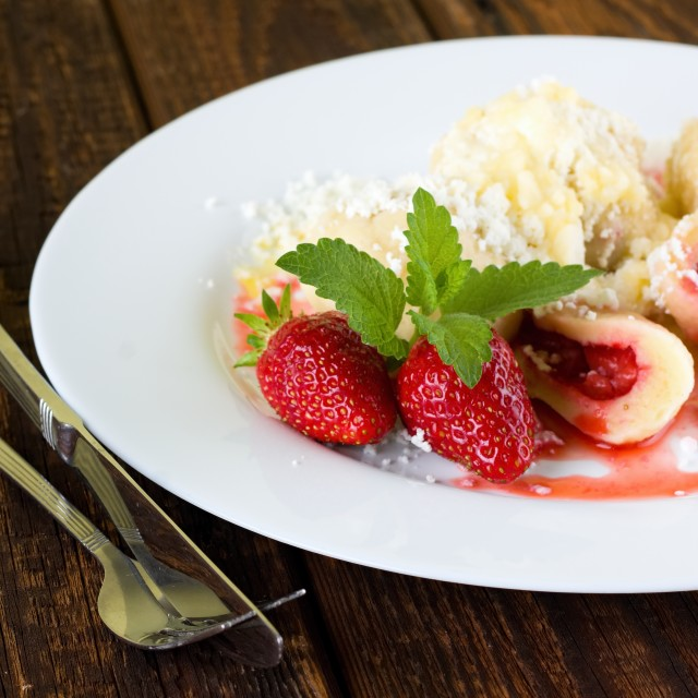 """Two strawberries with melissa on plate with fruit dumplings"" stock image"