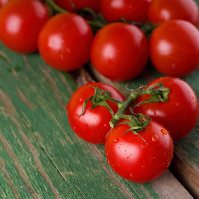 """""""Wet ripe juicy tomatoes on green table"""" stock image"""