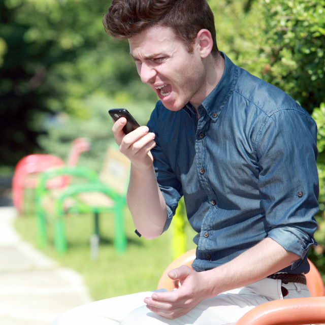 """""""Young man shouting on telephone in the park"""" stock image"""