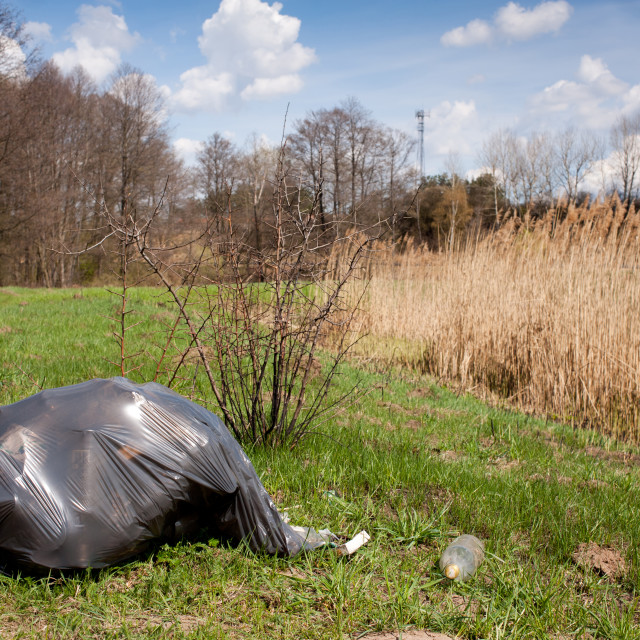 """Illegal scatter garbage in black plastic bag"" stock image"