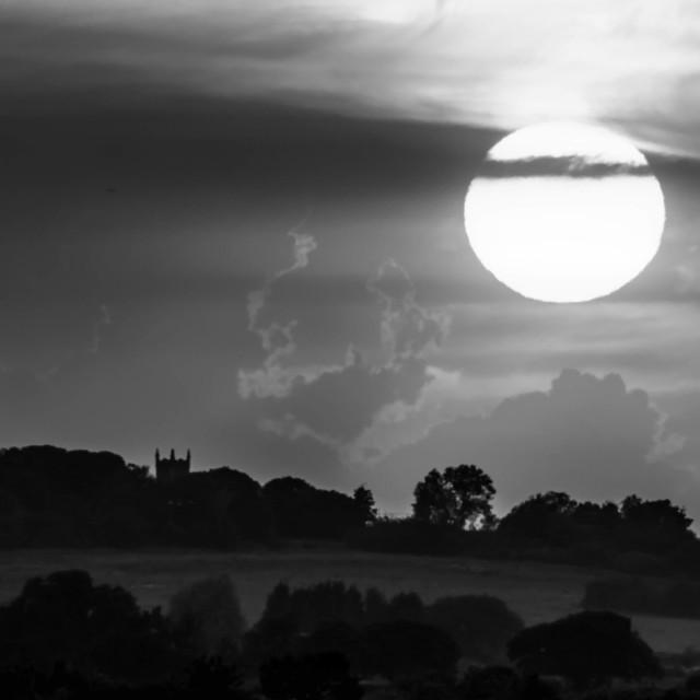 """Sun setting in monochrome"" stock image"