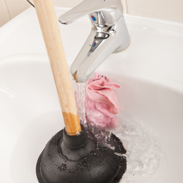 """black tool sink plunger in bathroom sink"" stock image"