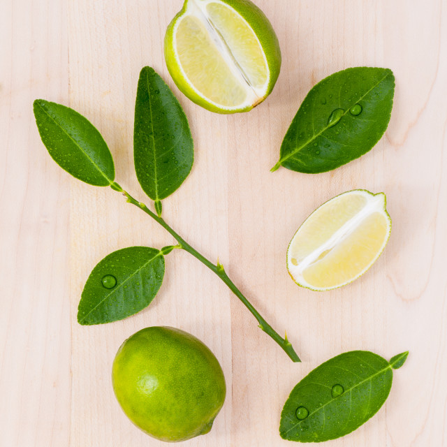 """Fresh lime and lime slice on wooden background with lime leaf."" stock image"